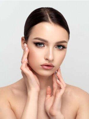 Naklejka Young beautiful woman touching her face