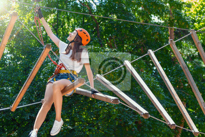 Naklejka Young beauty female woman adult wears protective helmet having fun in extreme rope park, amusement park. Sitting in rope bridge at green nature forest. Active healthy lifestyle in spring or summer.