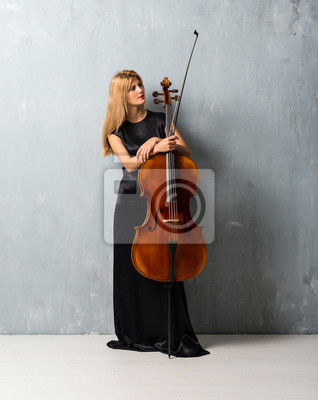 Naklejka Young blonde girl with her cello on textured wall background