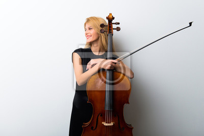 Naklejka Young blonde girl with her cello posing on white wall