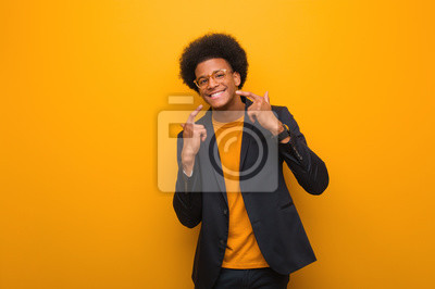 Naklejka Young business african american man over an orange wall smiles, pointing mouth