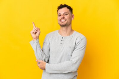 Naklejka Young caucasian handsome man isolated on yellow background happy and pointing up