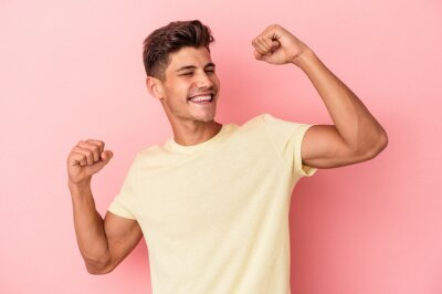 Naklejka Young caucasian man isolated on pink background celebrating a special day, jumps and raise arms with energy.