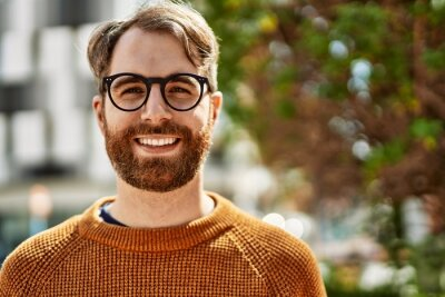 Naklejka Young caucasian man with beard wearing glasses outdoors on a sunny day