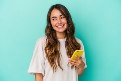 Naklejka Young caucasian woman holding a mobile phone isolated on blue background looks aside smiling, cheerful and pleasant.
