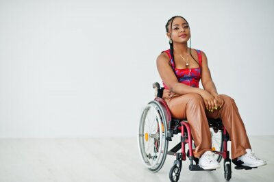 Naklejka Young disabled African American woman in wheelchair against white wall.