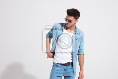 Naklejka Young fashion man holding adjusting his jacket