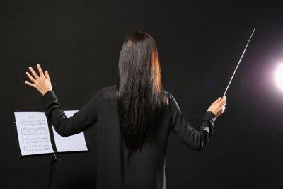 Naklejka Young female conductor on dark background