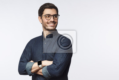 Naklejka Young handsome business man dressed in casual denim shirt with smartwatch on wrist, isolated on gray background