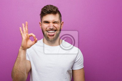 Naklejka Young handsome caucasian man winks an eye and holds an okay gesture with hand.