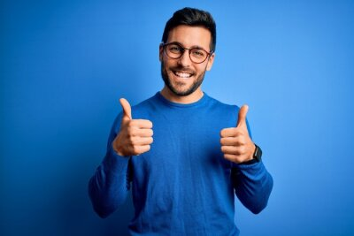 Naklejka Young handsome man with beard wearing casual sweater and glasses over blue background success sign doing positive gesture with hand, thumbs up smiling and happy. Cheerful expression and winner