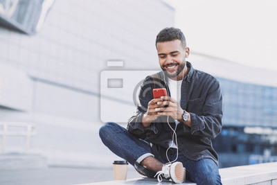 Naklejka Young handsome men using smartphone in a city. Smiling student man texting on his mobile phone. Coffee break. Modern lifestyle, connection, business concept