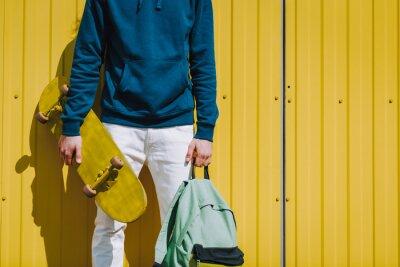 Naklejka Young hipster man holding skateboard and sack