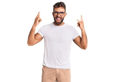Naklejka Young hispanic man wearing casual clothes and glasses shouting with crazy expression doing rock symbol with hands up. music star. heavy music concept.