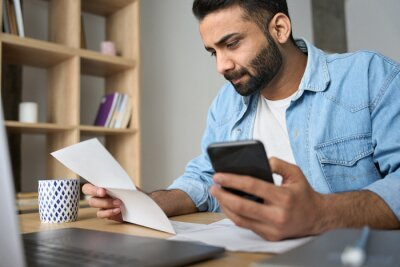 Naklejka Young indian businessman holding phone reading bank receipt calculating taxes, ethnic man using smartphone mobile application checking bill document, managing money finances, loan expenses.
