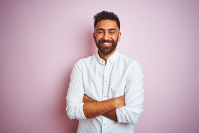Naklejka Young indian businessman wearing elegant shirt standing over isolated pink background happy face smiling with crossed arms looking at the camera. Positive person.