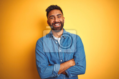 Naklejka Young indian man wearing denim shirt standing over isolated yellow background happy face smiling with crossed arms looking at the camera. Positive person.