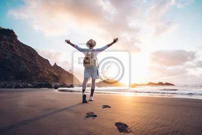 Naklejka Young man arms outstretched by the sea at sunrise enjoying freedom and life, people travel wellbeing concept