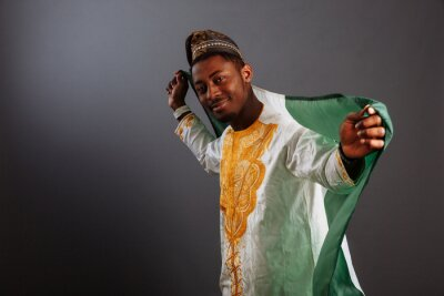 Naklejka Young man in yoruba and national clothes holding Nigeria Flag in gray Background, Flag of Nigeria.