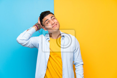 Naklejka Young man over isolated colorful background having doubts and with confuse face expression