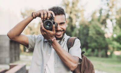 Naklejka Young man photographer takes photographs with dslr camera in a city. Travel, vacations, professional freelance work and active lifestyle concept