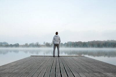 Naklejka Young man standing alone on wooden footbridge and staring at lake. Thinking about life. Mist over water. Foggy air. Early chilly morning. Peaceful atmosphere in nature. Enjoying fresh air. Back view.