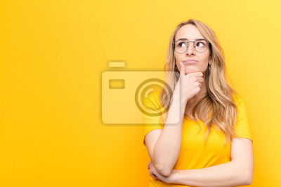 Naklejka young pretty blonde woman thinking, feeling doubtful and confused, with different options, wondering which decision to make against flat color wall