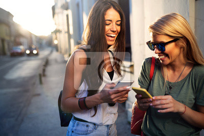 Naklejka young pretty woman friends posing in the street with phone