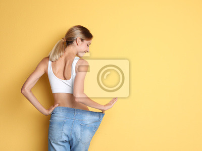 Naklejka Young slim woman in old big jeans showing her diet results on color background