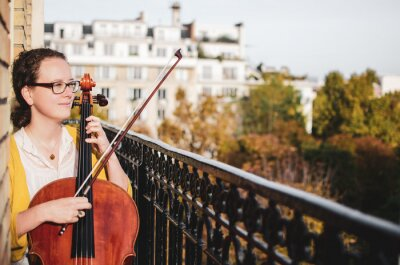 Naklejka Young smiling female cellist plucking cello strings on a beautiful balcony
