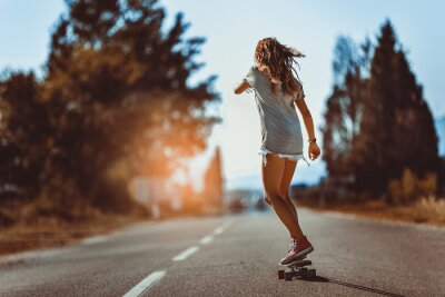 Naklejka Young sporty woman riding on the skateboard on the road.