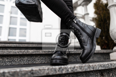 Naklejka Young trendy woman in stylish leather black boots in jeans with a bag stands on the stone steps in the city. Close up of female legs in fashion footwear. New collection of shoes and accessories.