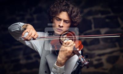 Naklejka young violinist playing violin.
