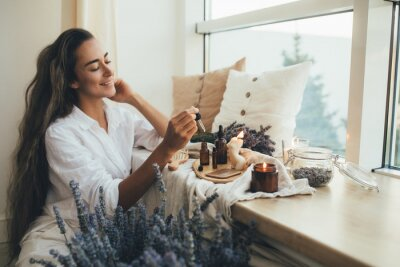 Naklejka Young woman applying natural organic essential oil on hair and skin. Home spa and beauty rituals.