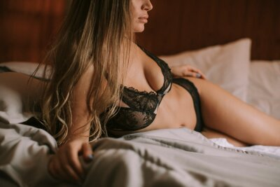 Naklejka Young woman in lingerie lying on the bed