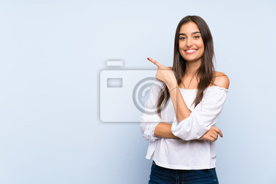 Naklejka Young woman over isolated blue background pointing finger to the side