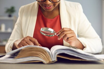 Naklejka Young woman sitting at desk, holding magnifying glass and reading book. Businesswoman, business auditor, teacher, professor searching for information, fact checking, consulting professional literature