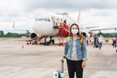 Naklejka Young woman wearing a face mask at the airport, New normal lifestyle concept