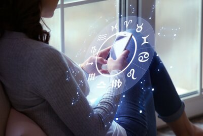 Naklejka Young woman with mobile phone reading astrological forecast at home