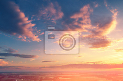 Zachmurzone niebo o zachodzie słońca. Wieczór na wsi
