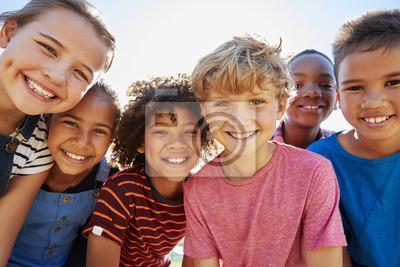 Naklejka Zamknij się pre-nastolatków przyjaciele w parku uśmiecha się do kamery