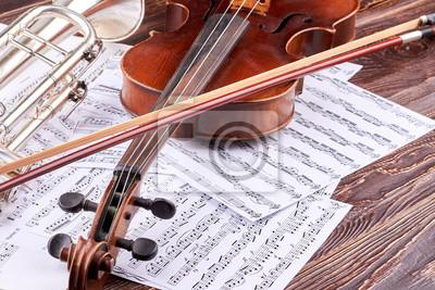 Naklejka Zamknij się skrzypce, łuk i nuty. Vintage skrzypce, trąbka i nuty na drewnianym tle. Tło instrumentów muzyki klasycznej.