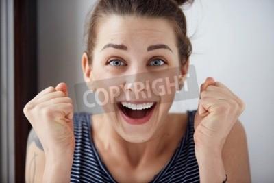 Naklejka Zaskoczony kobieta z rękami w górze zaskoczony lub zszokowany przez niespodziewane wieści trzyma blisko dłonie i pokazując szczęśliwy wyraz. Młoda dorosła kobieta na greybackground
