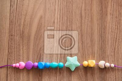 750209565f856 Naklejka Zawieszki dziewczynki silikonowe kulki z fioletowym liny na  drewnianym tle