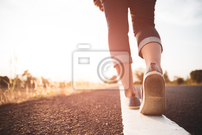 Naklejka Zbliżenie kobiety odprowadzenie w kierunku na drogowej stronie. Koncepcja kroku.