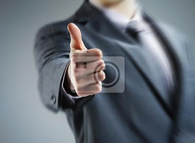 Zbliżenie młodego biznesmena pokazując kciuk do góry.