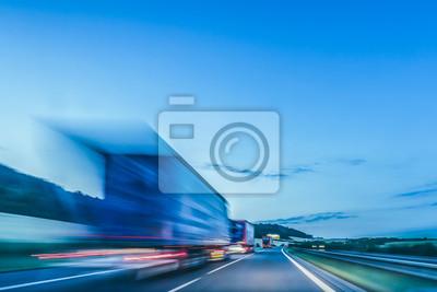 Naklejka Zdjęcie w tle autostrady. Ciężarówka na autostradzie, rozmycie ruchu, lekkie ślady. Wieczorne lub nocne ujęcie ciężarówek wykonujących logistykę i transport na autostradzie.