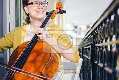Naklejka Żeński muzyk klasyczny uśmiecha się i gra na wiolonczeli na balkonie
