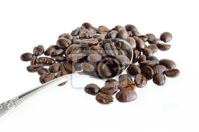 Ziarna kawy i srebrna łyżeczka na białym