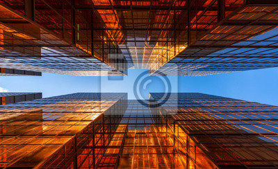 Naklejka Złoty budynek z niebieskim niebem. Szklane okna nowoczesnych wieżowców biurowych. projekt fasady. Architektury powierzchowność dla pejzażu miejskiego tła.